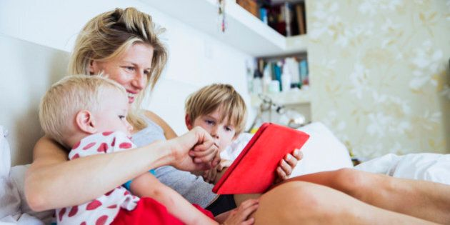 Mother with her sons watching tablet in