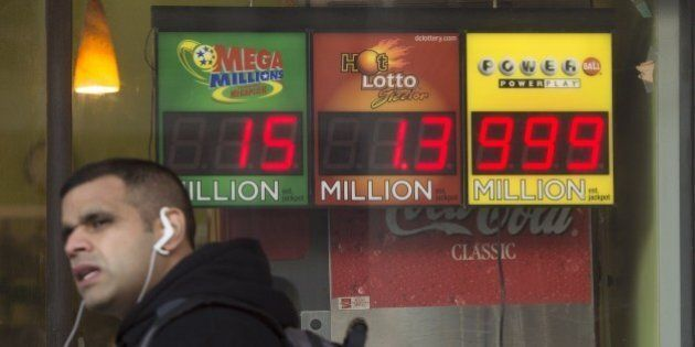 A man walks past a sign showing a Powerball prize of $999 million, the largest jackpot winnings that...