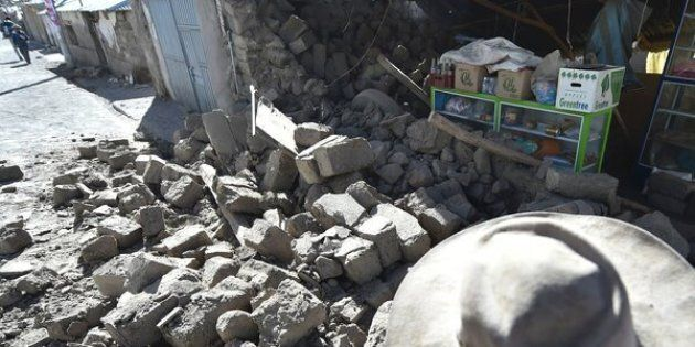 A woman observes the damage in her home on August 15, 2016 in the Andean town of Yanque in southern Peru caused by a 5.3 magnitude earthquake that struck this remote picturesque region in the state of Arequipa on Sunday night.At least four other people also died and 68 were injured, most by toppling buildings. Rescue and aid efforts have been hampered by more than 60 replica aftershocks that have rocked the area, which is popular with tourists, in the past 24 hours. / AFP / Jose Sotomayor Jimenez        (Photo credit should read JOSE SOTOMAYOR JIMENEZ/AFP/Getty Images)