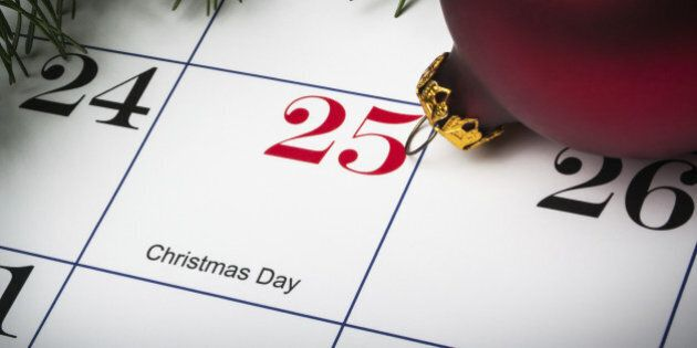 Close up of calendar on December 25th, Christmas day, with evergreens and an
