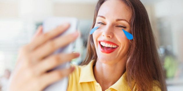 Portrait of beautiful female smiling, crying and lookining at a phone