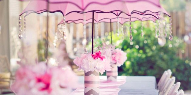 Table set for a baby shower for a girl. With pink umbrellas with crystals and pink