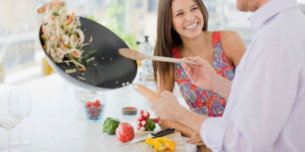 Woman watching husband flipping stirfry in the