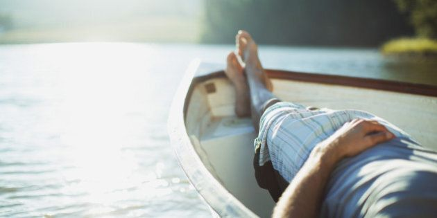 Man laying in rowboat on tranquil