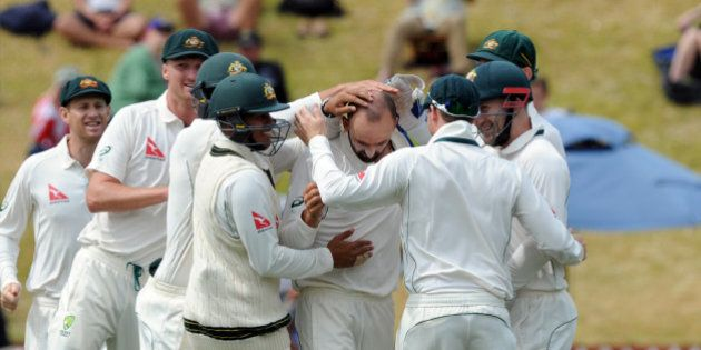Australia's Nathan Lyon, centre, surrounded by team mates after bowling New Zealand's BJ Watling...