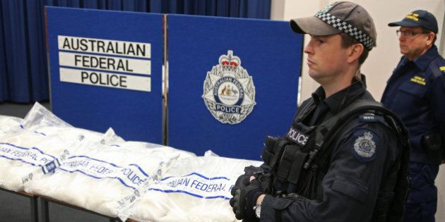 Police officers stand guard over methamphetamine seized by the Australian Federal Police in Sydney, Friday, May 15, 2015. A Hong Kong man has been charged with the importation of the 150 kilogram (330 pound) haul that police say has a potential street value of up to $100 million (US $80.65 million). (AP Photo/Rick Rycroft)