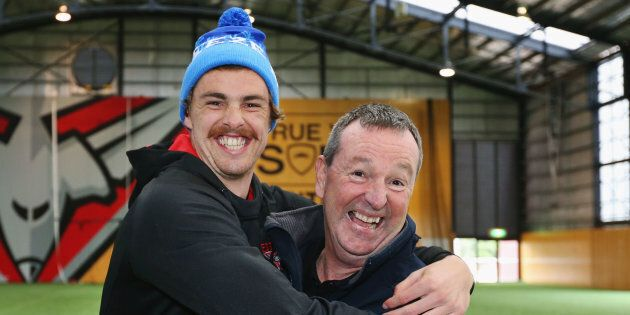 Bomber's legend Neale Daniher (R) gets a hug from nephew Joe Daniher after a cheque presentation to fight...