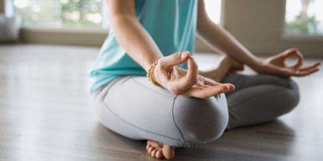 Woman in lotus position practicing mudra