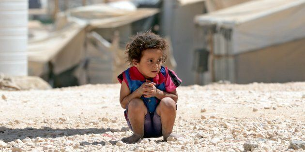 This is no normal life: a young syrian child plays in the dirt at Za'atari refugee
