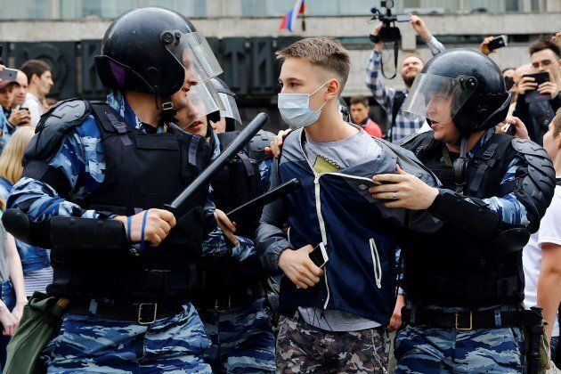 Russian riot police brandished batons and released pepper spray onto thousands of protestors in Moscow on Monday.