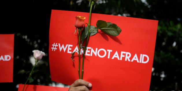 An activist holds a poster during a rally condemning Thursday's attack, outside the Starbucks cafe where...