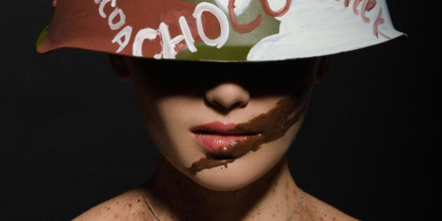 Beautiful woman with chocolate helmet, camouflage and badge on the neck
