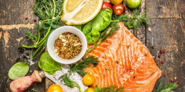 fresh salmon fillet with fresh healthy herbs,vegetables, oil and spices on rustic wooden background, top view