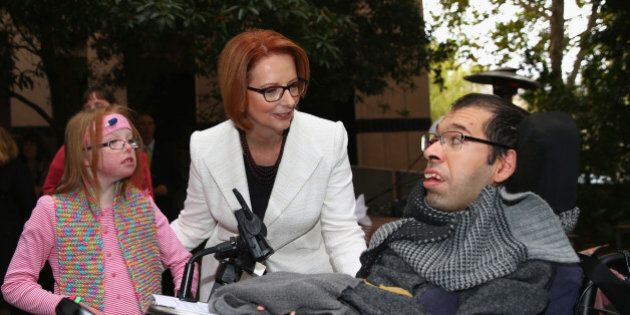 MELBOURNE, AUSTRALIA - MAY 01:  Australian Prime Minister Julia Gillard meets Sophie Dean (L) and Dr George Taleporos (R) from the disabled community after a press conference at the Commonwealth Parliamentary Office on May 1, 2013 in Melbourne, Australia. Gillard has announced that the Federal Government will increase the Medicare levy on income tax from 1.5 to two percent to help fund the National Disability Insurance Scheme (NDIS). The levy will begin on July 1, 2014 and is expected to raise around $3.2 billion annually towards the NDIS which is expected to cost $8 billion per year. (Photo by Robert Cianflone/Getty Images)