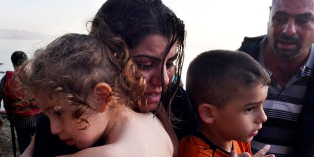 KOS, GREECE - AUGUST 15: A Syrian family arrives at a beach on the Greek island of Kos after crossing...