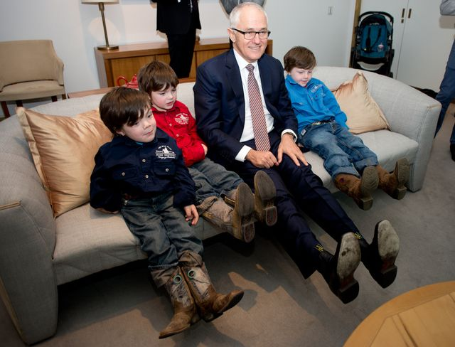 Beau Cosgrove (far left) with his brothers, comparing 'cowboy boots' with Prime Minister Malcolm Turnbull.