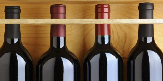 Closeup of four red wine bottles in a wooden