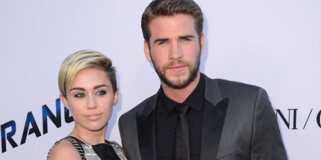 Actor Liam Hemsworth, right, and singer Miley Cyrus arrive at the US premiere