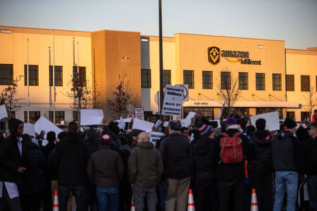 Demonstrators shout slogans and hold placards during a protest at the Amazon fulfillment center in Shakopee,...
