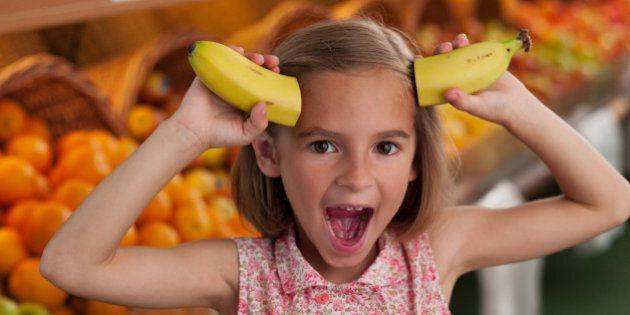 Girl holding bananas as horns in grocery