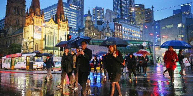 MELBOURNE, AUSTRALIA - JULY 31:  People shelter from the rain under umbrellas as they cross the road from Federation Square on July 31, 2014 in Melbourne, Australia. Temperatures dropped and strong winds of over 100mk/h hit Melbourne this afternoon, bringing rain and hail across the state.  (Photo by Scott Barbour/Getty Images)