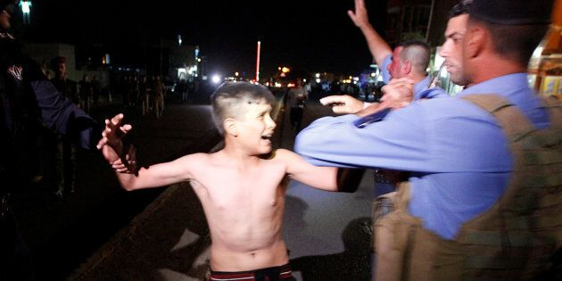 Iraqi security forces detain a boy after removing a suicide vest from him in Kirkuk, Iraq, Aug. 21,