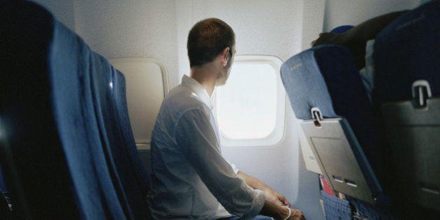 Man sitting in passenger plane, looking through window, side