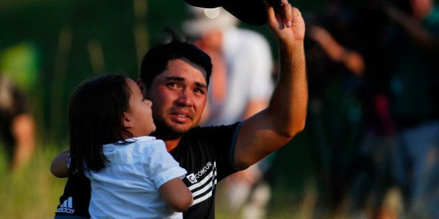 SHEBOYGAN, WI - AUGUST 16: Jason Day of Australia walks off the 18th green with his son Dash after winning...