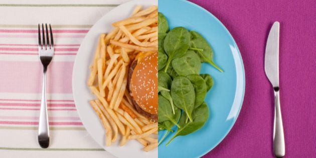 stock image of low fat healthy spinach leaves against unhealthy greasy burger with french fries. diet