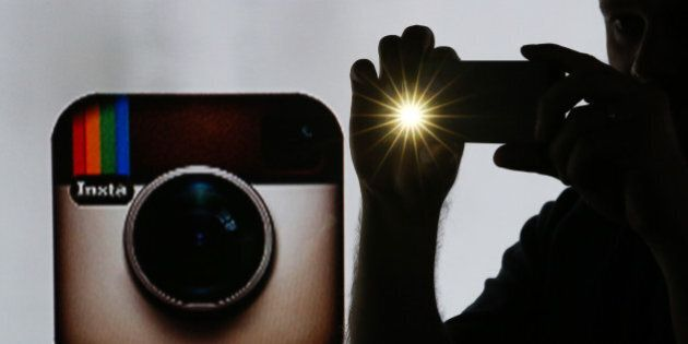 A man takes a photograph with a mobile device whilst standing against an illuminated wall bearing Instagram...