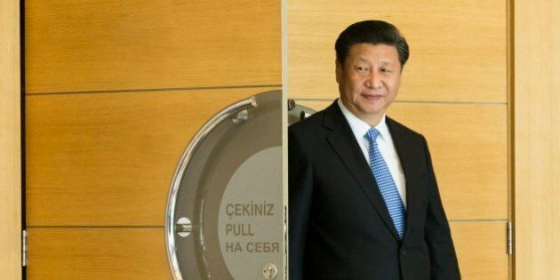 Chinese President Xi Jinping enters a hall to pose for a photo of leaders of BRICS meeting prior the...