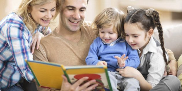 Smiling parents reading a book to their little