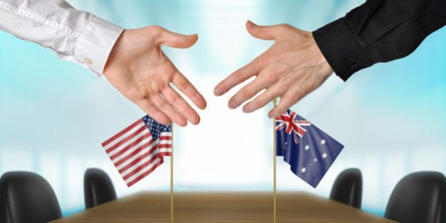 Two diplomats from United States and Australia extending their hands for a handshake on an agreement...