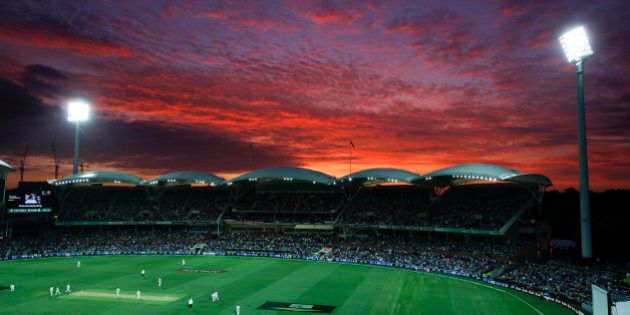 """Lights illuminate the Adelaide Oval as the sun sets during the first night session of the cricket test between Australia and New Zealand in Adelaide, Friday, Nov. 27, 2015. This match is the sport's first ever day-night test and the use of the """"experimental"""" pink leather ball replacing the standard-issue red for the first time in a format that dates back to the 1870s. (AP Photo/Rick Rycroft)"""
