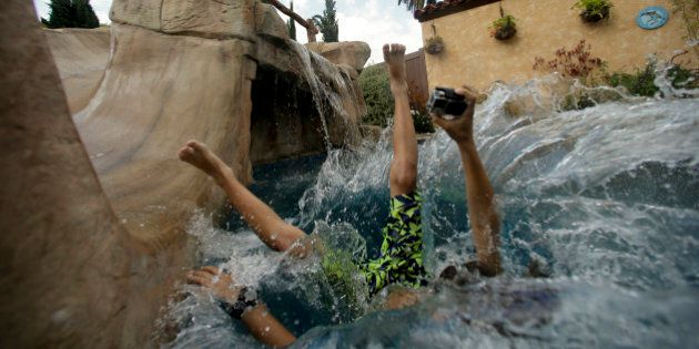 In this photo taken on Thursday, May 21, 2015, Jake Hall, 10, dives into a backyard pool in Long Beach,...