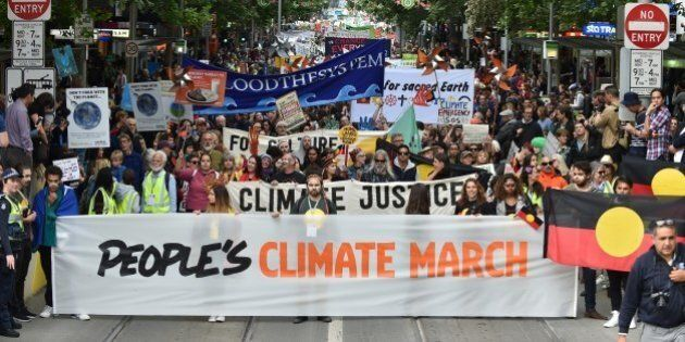 People march along a road during a rally calling for action on climate change in Melbourne on November...