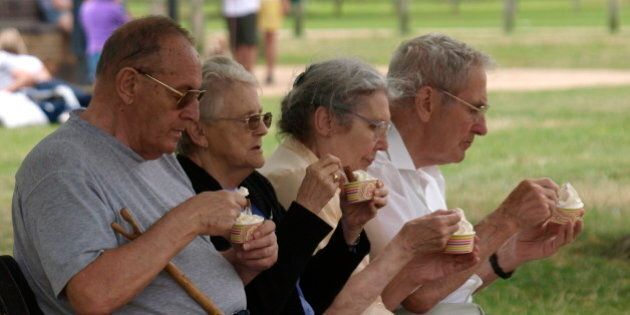 Four pensioners sat on a park bench eating ice cream, Stratford upon Avon, UK. (Photo By: Education Images/UIG...