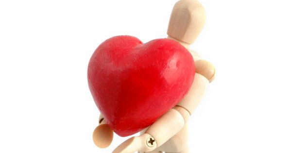 A wooden mannequin holds a symbolic heart.