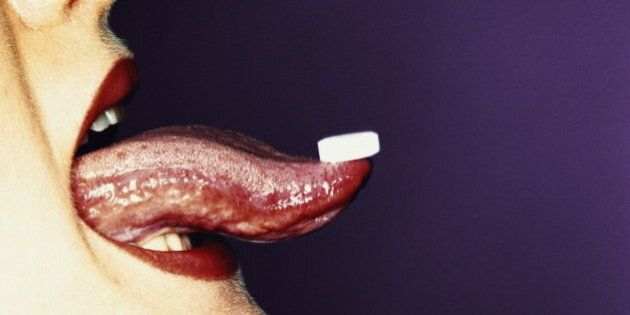 Woman's tongue with white tablet balancing on tip, profile,