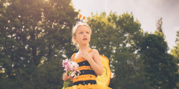 A child dressed as a Bumblebee looks up in a stoic pose with a handful of
