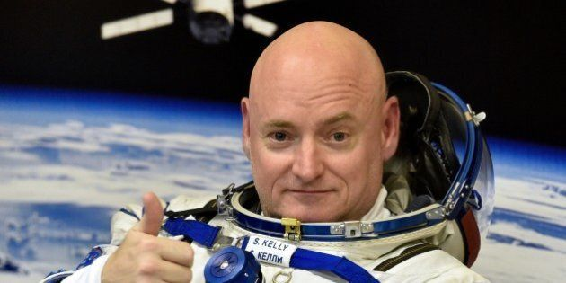 US astronaut Scott Kelly gestures as his space suit is tested at the Russian-leased Baikonur cosmodrome,...
