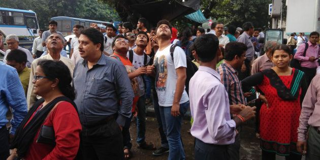 People stand outside their offices after they rushed outdoors following tremors in Kolkata,