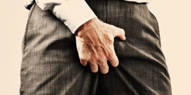 Cropped view of businessman in formal clothes grabbing his genitals through his clothes, maybe he's itchy...