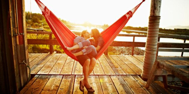 Husband and wife couple kissing in hammock on dock at sunset
