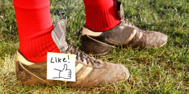 'Like' symbol on football players boots, while standing in a field ready to