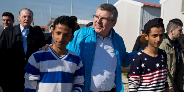 IOC President Thomas Bach, center, walks with two young refugees with former IOC President Jacques Rogge...