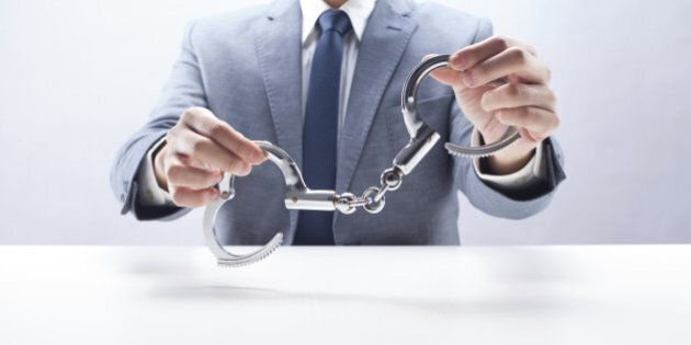 Businessman holding handcuffs at the