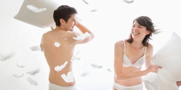Couple in underwear enjoying pillow fight