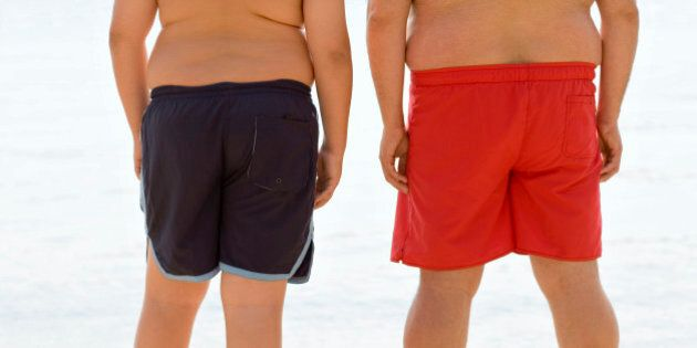 Overweight man and boy standing at