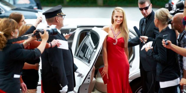 A stunning young starlet emerging from a limousine to fanfare and paparazzi demand on the red